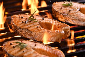 Grilled salmon fish with various vegetables on the flaming grill Premium Photo