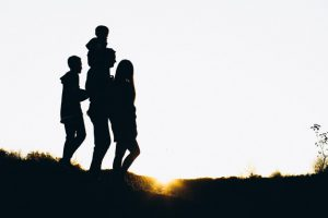 Silhouette of a family walking by the sunset time Free Photo
